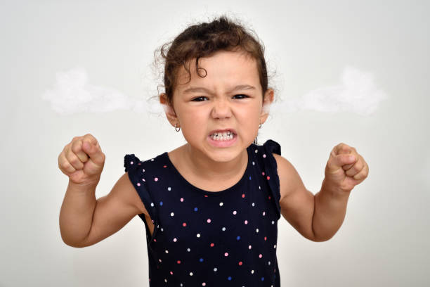 Angry and aggressive young girl with steam blowing out of her ears Angry and aggressive young girl with clenched teeth and fists and steam blowing out of her ears looking at the camera. Childhood and expressions concept. clenching teeth stock pictures, royalty-free photos & images