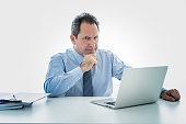 Angry and frustrated middle aged businessman overworked, upset and frustrated having too much work and staying extra hours at office. In Overtime, stress at work concept isolated in white background.