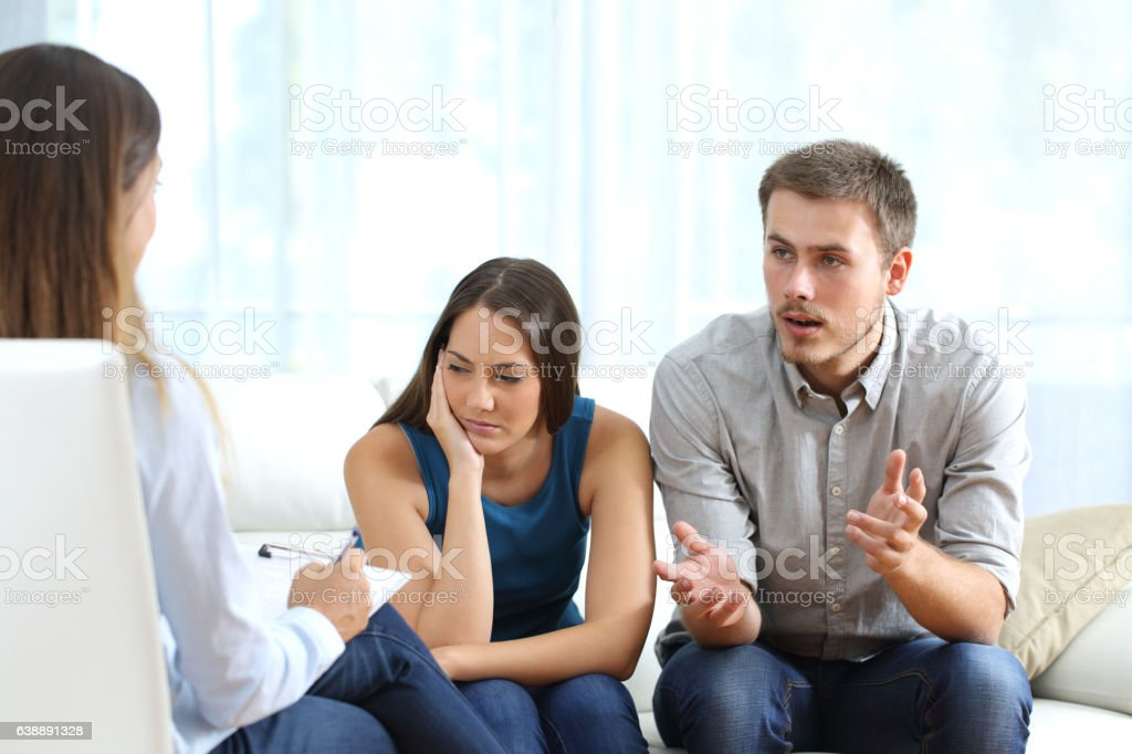 Angry and sad couple talking with a marriage counselor stock photo