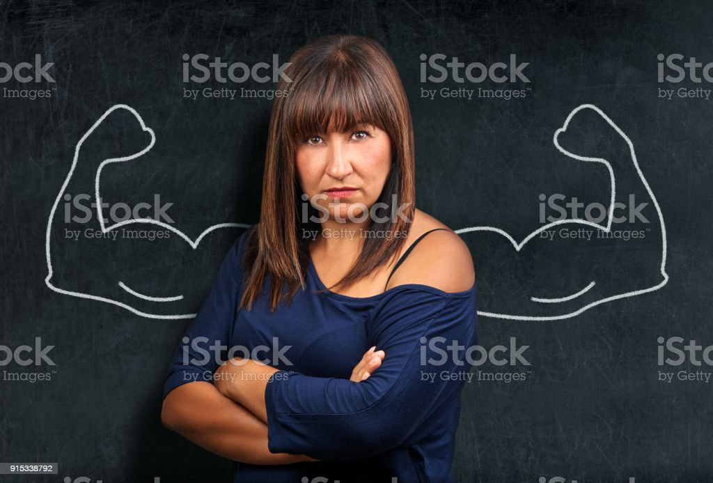 Angry and strong brunette woman at blackboard or chalkboard showing biceps stock photo