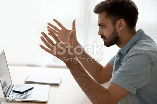 513396643 istock photo Angry annoyed young man mad about computer problem at work 1125572557