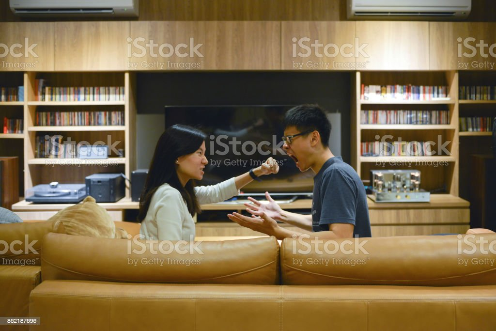 Angry Asian couple fighting in front of TV in living room at night