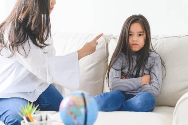Wütende asiatische Mutter sitzt mit kleiner Tochter, Mama schimpft für Disziplin schlechtes Verhalten kapriziöses Kind, Familie Generationen Probleme, Missverständnis Konzept – Foto