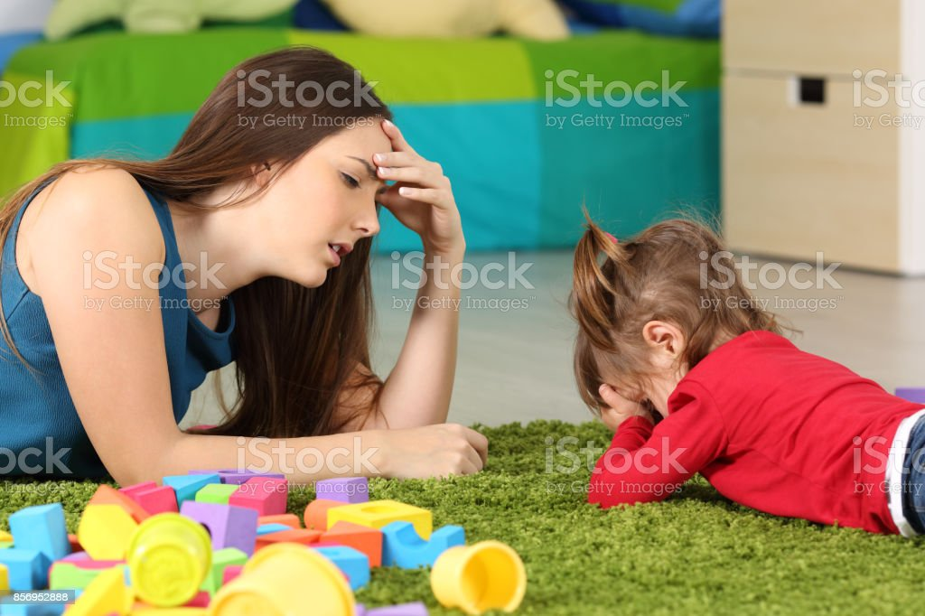 Angry baby and tired mother in a room stock photo