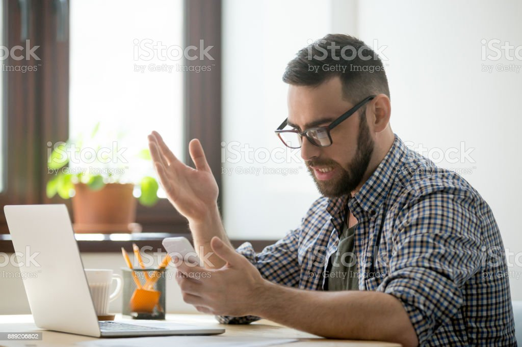 Angry bearded businessman annoyed with phone call in office stock photo