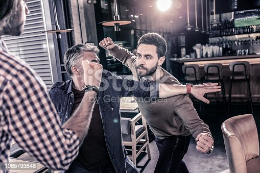 Expressing anger. Concentrated brunette male demonstrating his fists while looking at his opponent