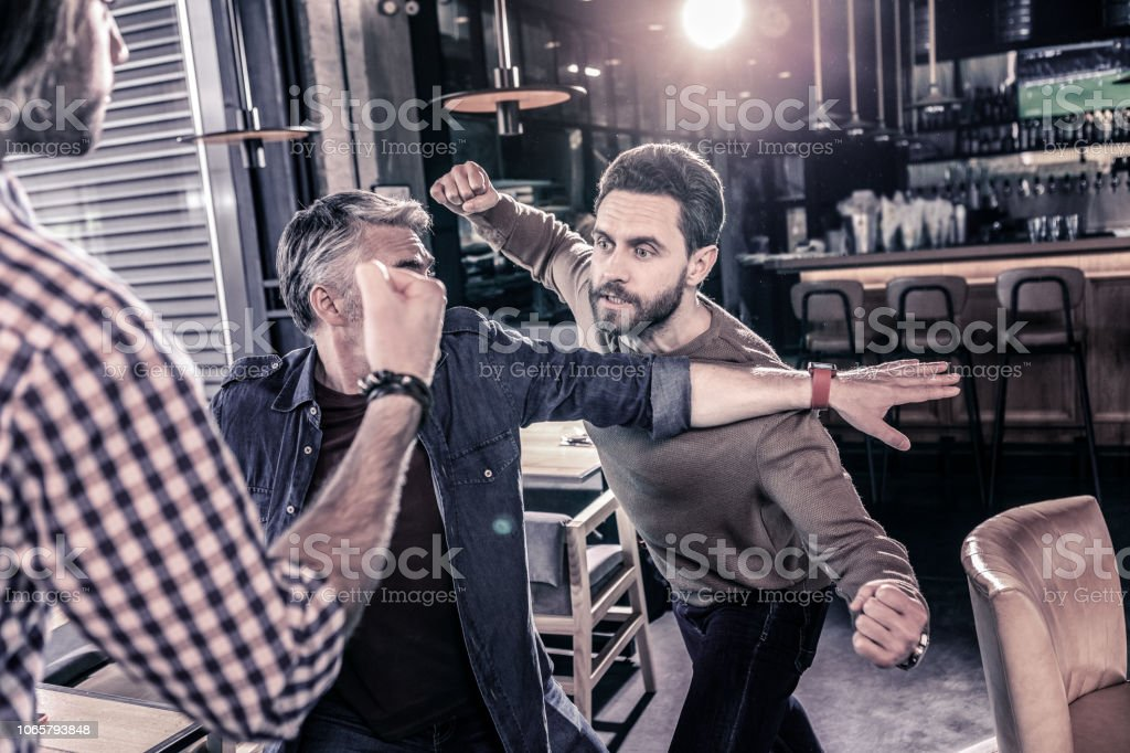 Angry bearded man going to beat his friend stock photo