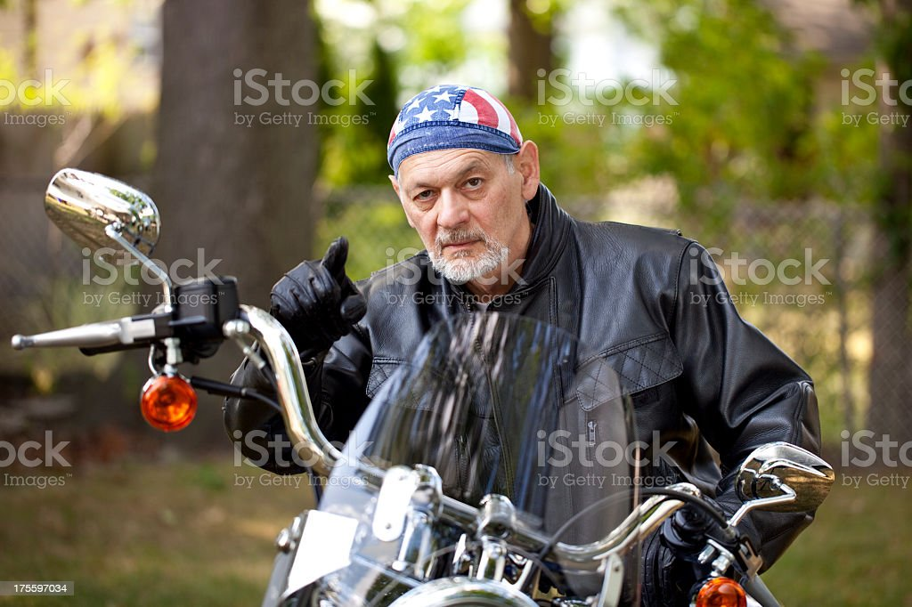 Angry Biker in leather jacket on motorcycle pointing toward camera stock photo