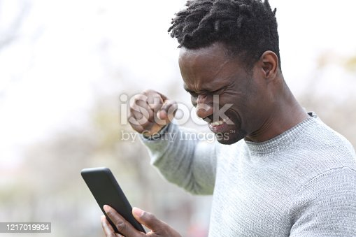 824614192 istock photo Angry black man checking content on smart phone 1217019934