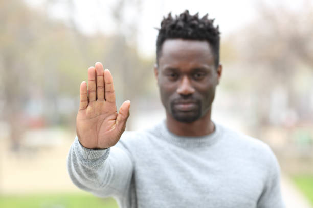 Angry black man gesturing stop outdoors Front view portrait of an angry black man gesturing stop showing hand palm outdoors in a park prettige verrassingen stock pictures, royalty-free photos & images