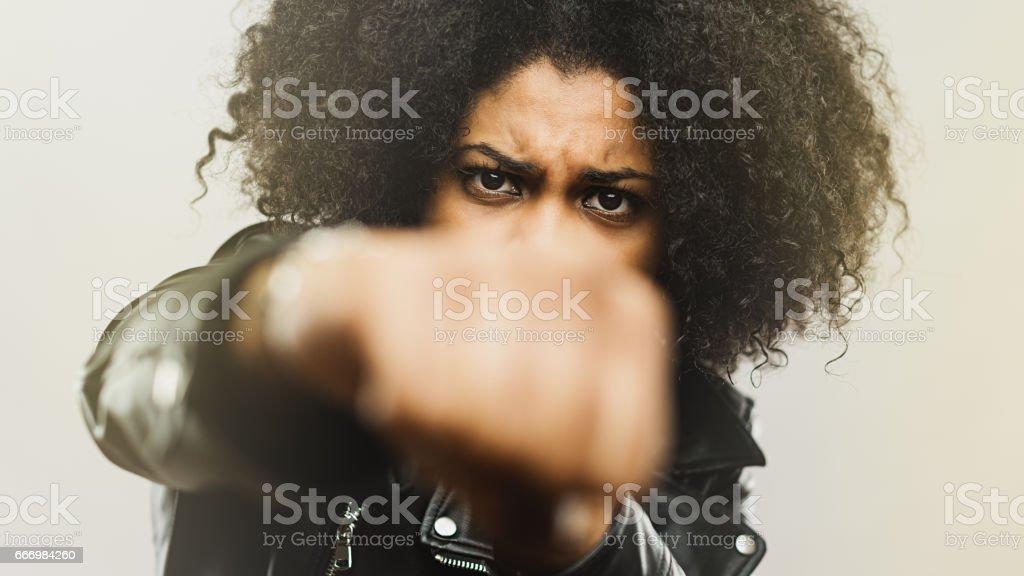 Angry black woman punching at camera stock photo