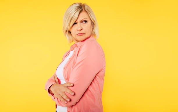 Angry blonde senior woman with crossed arms is posing over yellow background Angry blonde senior woman with crossed arms is posing over yellow background nettle stock pictures, royalty-free photos & images