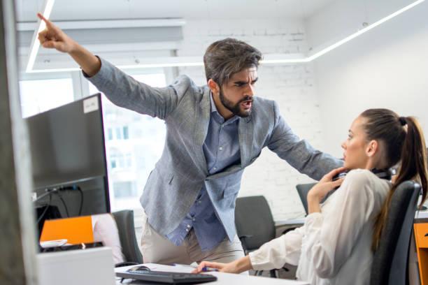 Wütender Chef feuert verärgerte Mitarbeiterin im Amt. Junge männliche Managerin schreit verängstigt und gestresstGeschäftsfrau an ihrem Arbeitsplatz. – Foto