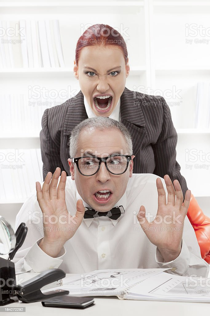 Angry boss harrasing her nerdy worker royalty-free stock photo