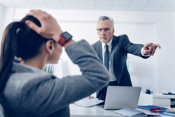 Angry boss outing his young office worker stock photo