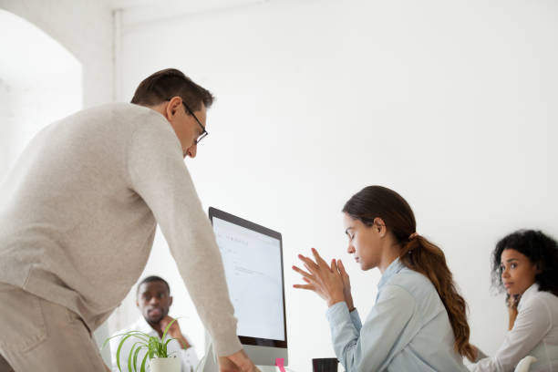 Angry boss scolding or firing upset intern in multiracial office stock photo
