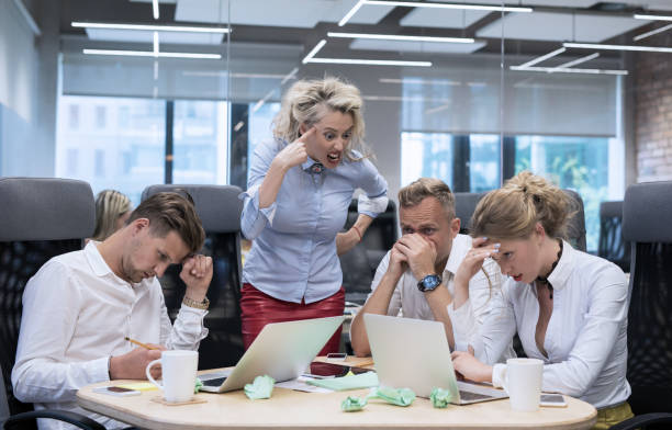 Angry boss shouting at employees stock photo