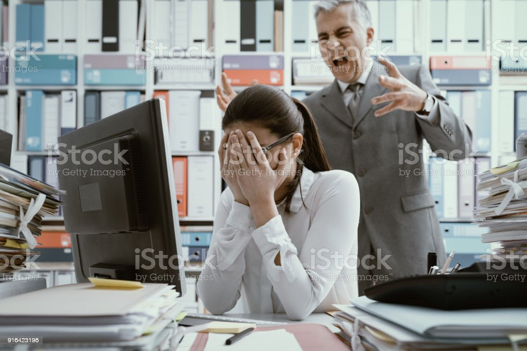 Angry boss yelling at his young employee stock photo