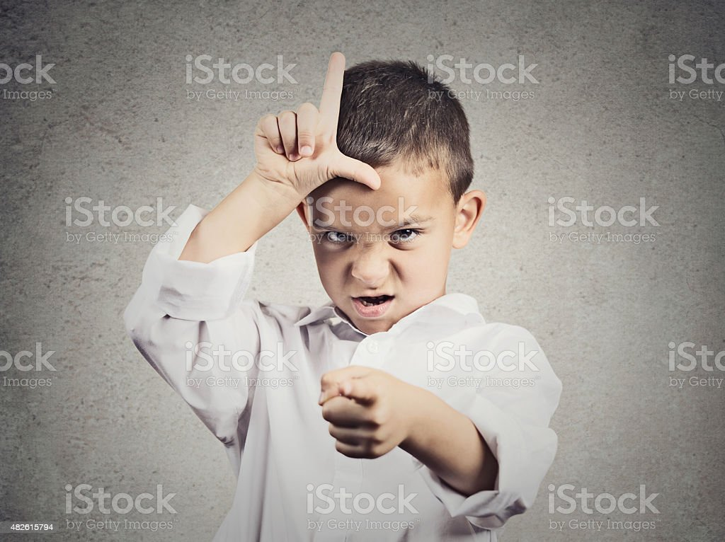 Angry boy displaying loser sign stock photo
