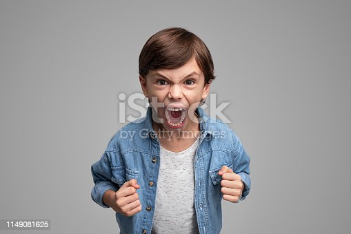 Boy in casual outfit clenching fists and shouting angrily at camera while standing on gray background