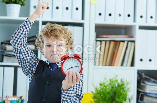 istock Angry boy trying to punch an alarm clock, standing in office. Lack of time, bad time management, overtime. 940995934