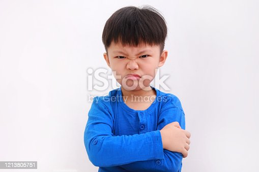 Portrait of little Asian boy with blue t-shirt, arm crossed, showing angry face, looking at the camera over white background.
