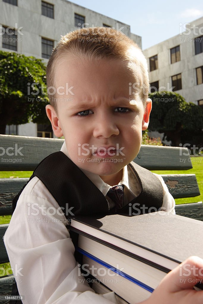 Angry Boy with Stack of Books stock photo
