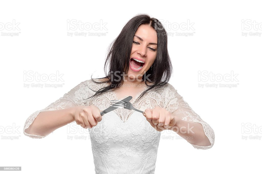 Angry bride with knife and fork. stock photo