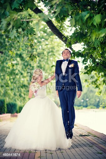 istock Angry Bride with one Hand holding the Groom in Air 493441674