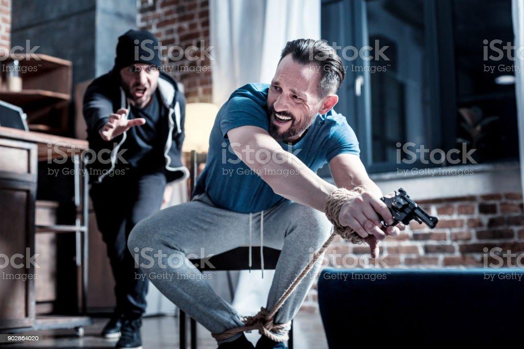 Assaltante com raiva tentando tirar a arma - foto de acervo