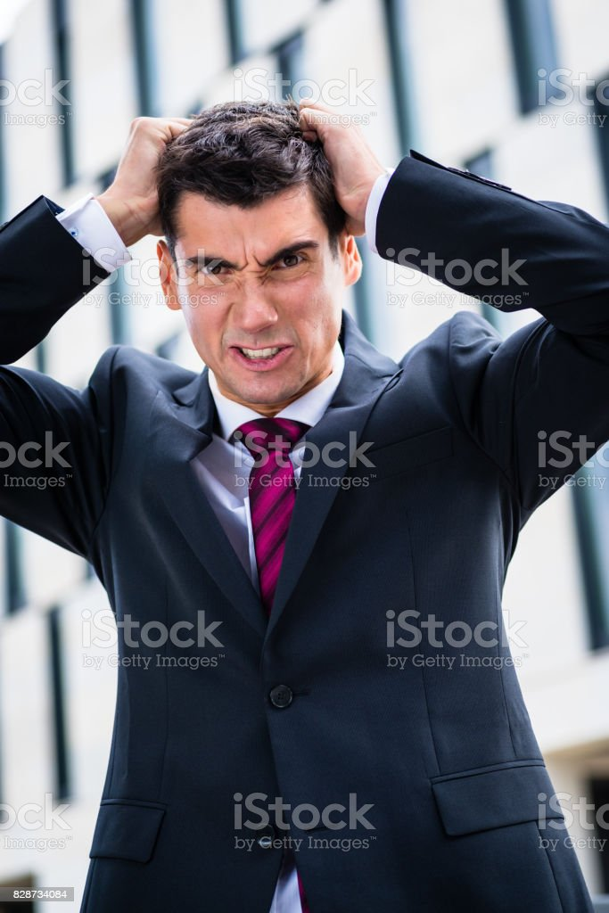 Angry business man tearing hair in despair stock photo