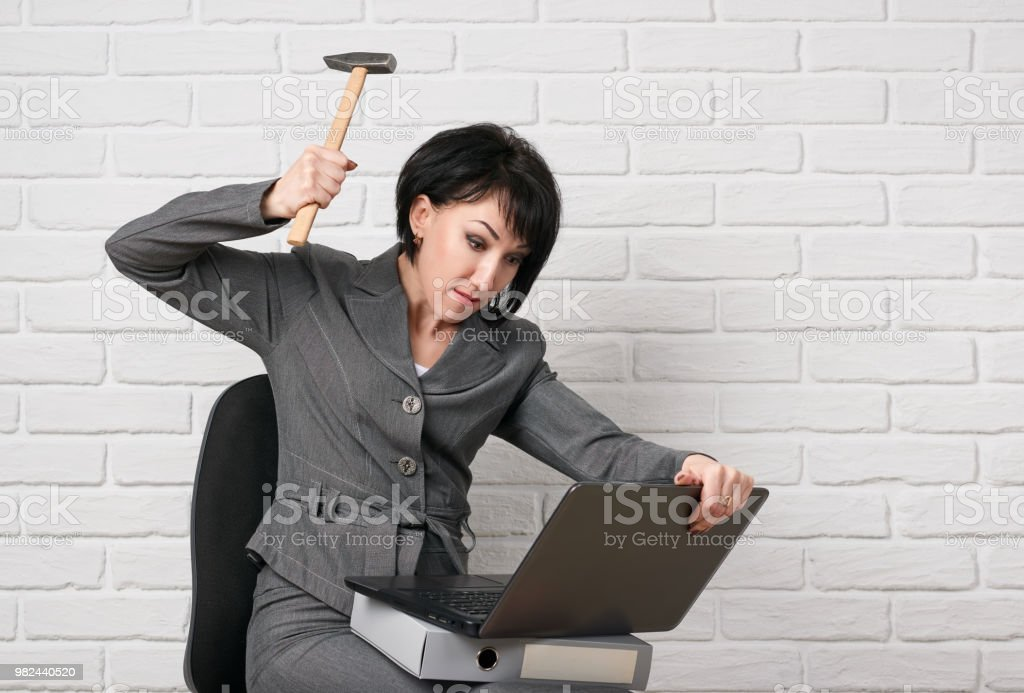 angry business woman with laptop and folders having stress, dressed in a gray suit poses in front of a white wall stock photo