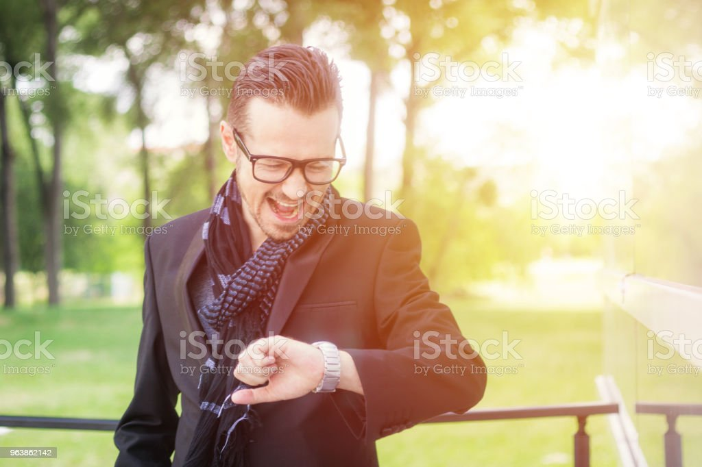Angry businessman checking time on wristwatch and screaming. - Royalty-free Adult Stock Photo