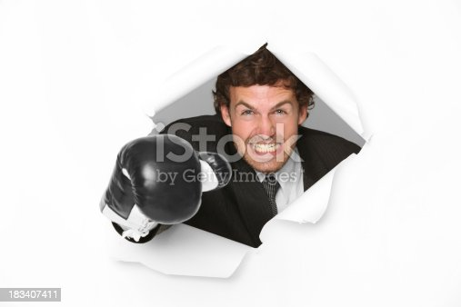 160558362 istock photo Angry businessman emerging through hole in paper 183407411