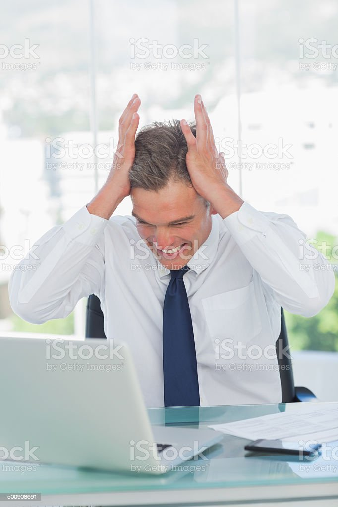 Angry businessman hands on his head stock photo