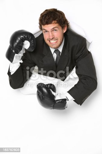 160558362 istock photo Angry businessman in boxing gloves emerging through a hole 183762603