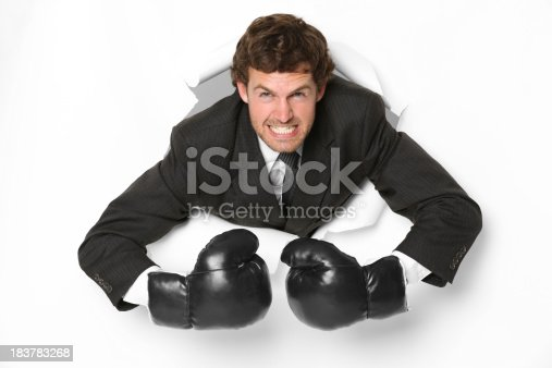 160558362 istock photo Angry businessman in boxing gloves emerging through a hole 183783268