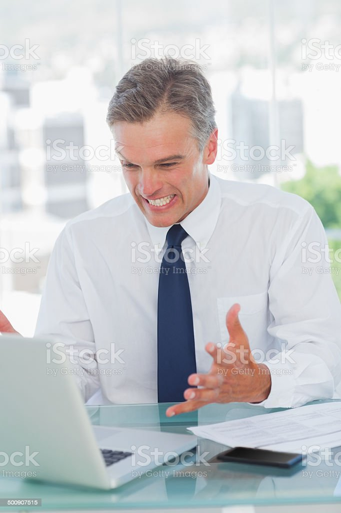 Angry businessman looking at his laptop stock photo