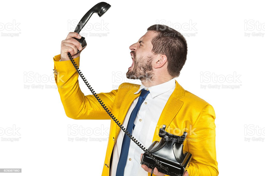 angry businessman screaming to the telephone handset stock photo