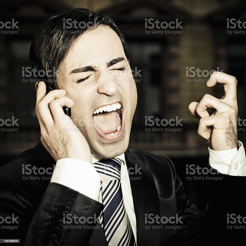 Angry businessman shouting into mobile phone royalty-free stock photo
