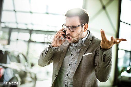 Young displeased businessman arguing with someone over smart phone while being in a car showroom.
