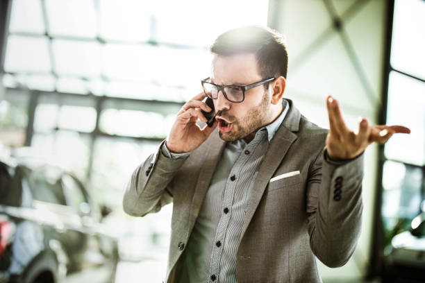 Angry businessman talking on cell phone in a car showroom. Young displeased businessman arguing with someone over smart phone while being in a car showroom. displeased stock pictures, royalty-free photos & images