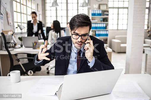 692461598 istock photo Angry businessman talking on smart phone, having problems 1041145728