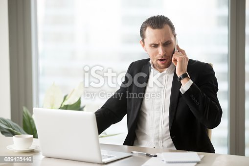 824614192 istock photo Angry businessman talking on the cellphone 689425446