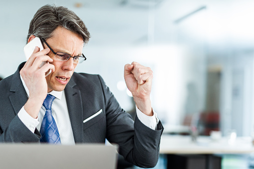istock Angry businessman talking to someone over cell phone in the office. 1178081365