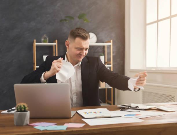 wütend geschäftsmann zerreißt ein dokument - kündigung arbeitsvertrag stock-fotos und bilder