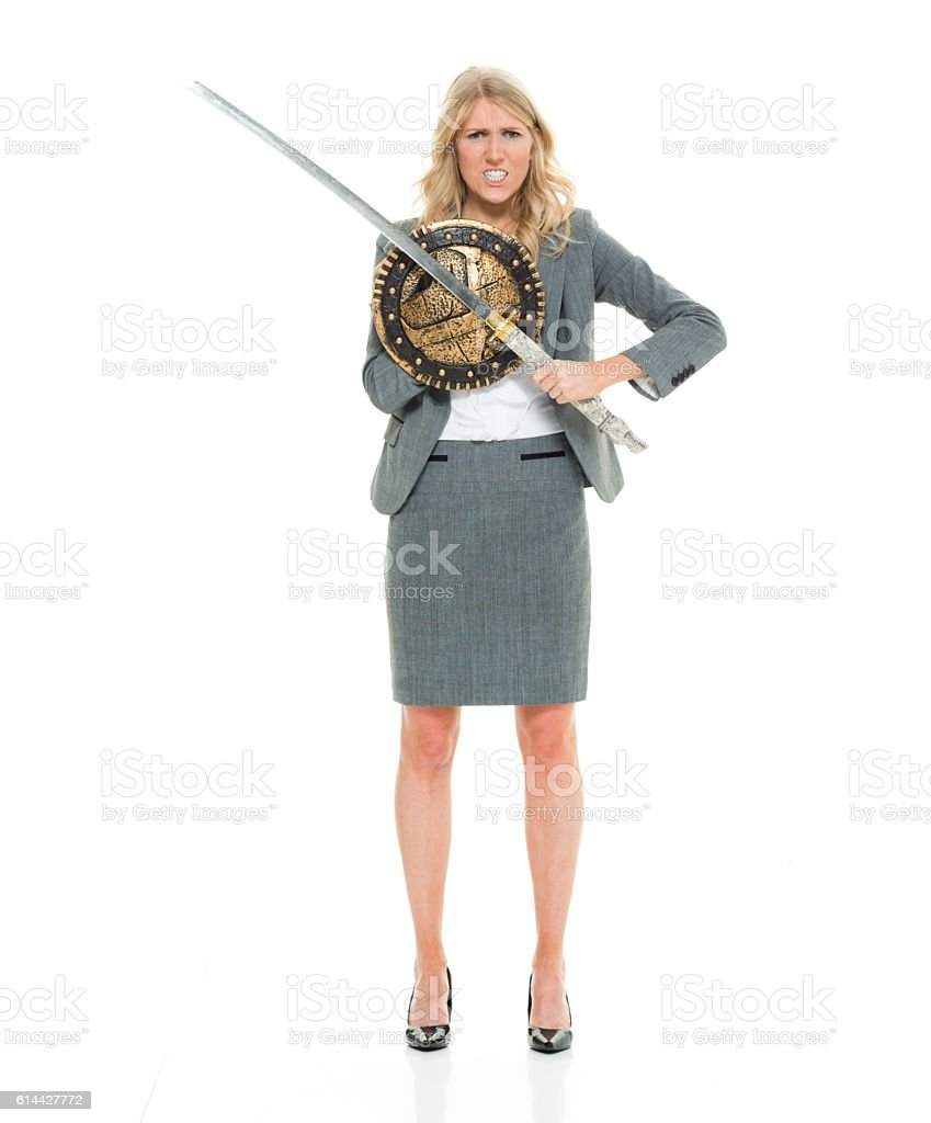 Angry businesswoman in action with sword stock photo