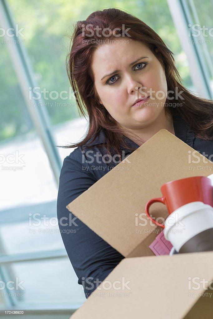 Angry businesswoman leaving office after being fired or laid off stock photo