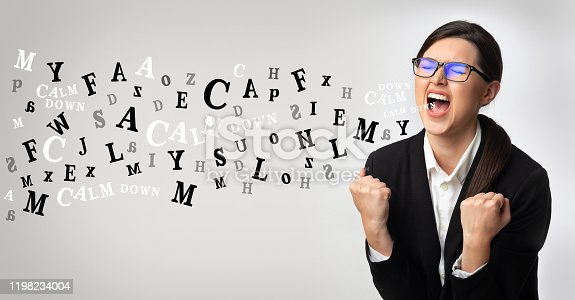 Problems at work concept. Portrait of angry businesswoman screaming, alphabet letters coming out of open mouth over light background