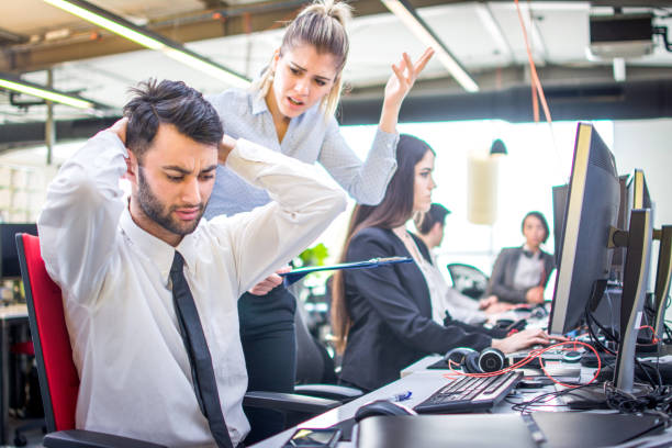 Angry businesswoman shouting at her worker with hands behind head in office stock photo